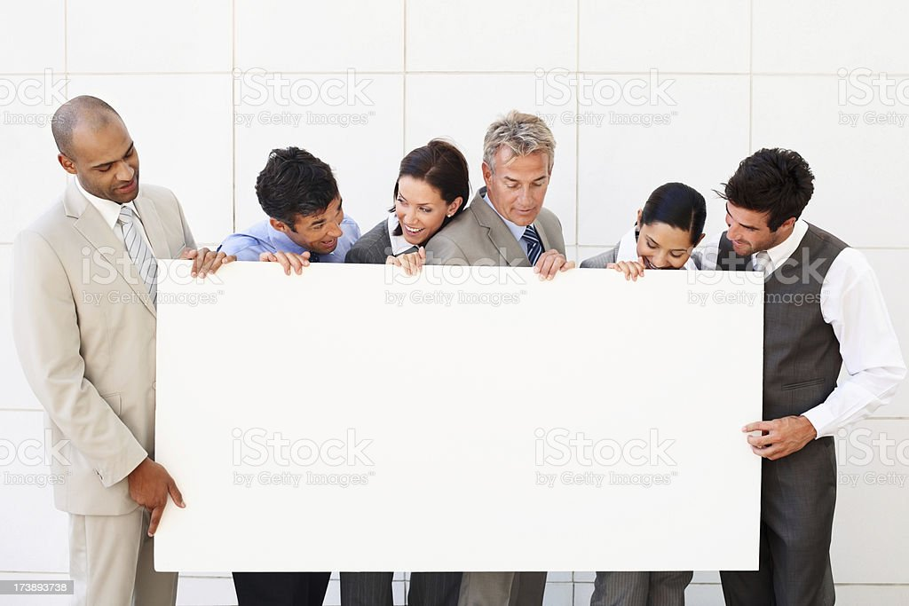 Group of business colleagues holding billboard royalty-free stock photo