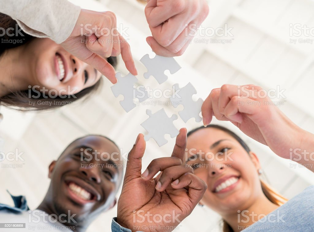 Group of business people assembling a puzzle stock photo