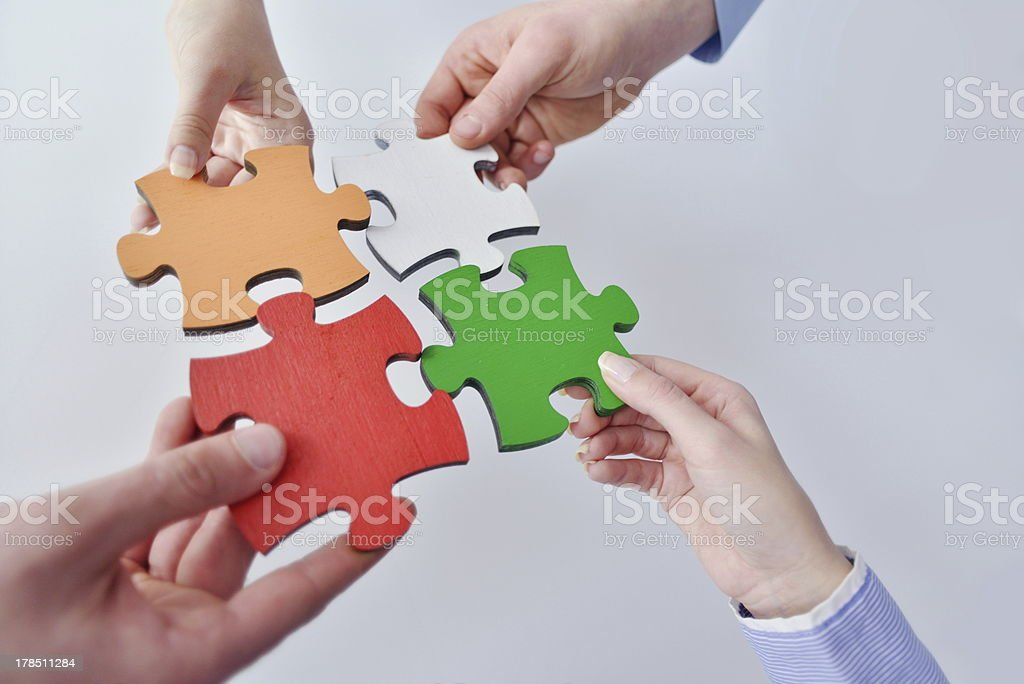Group of business people assembling jigsaw puzzle royalty-free stock photo