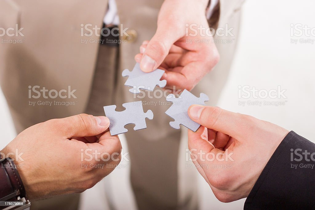 Group of business people assembling jigsaw puzzle. Teamwork. royalty-free stock photo