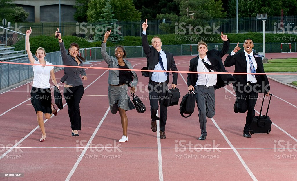 A group of business people crossing the finish line stock photo