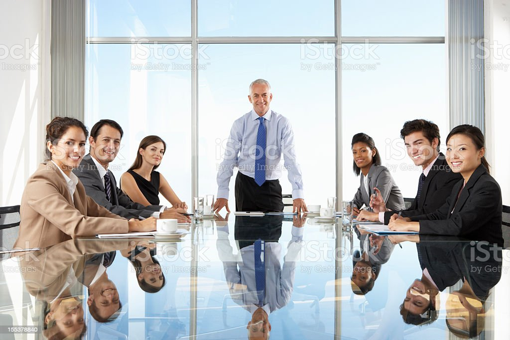 Group Of Business People Having Board Meeting Around Glass Table stock photo