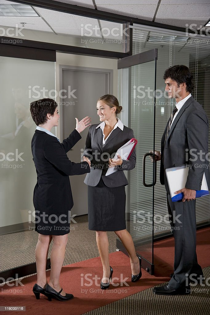 A group of business people in a meeting room shaking hands stock photo