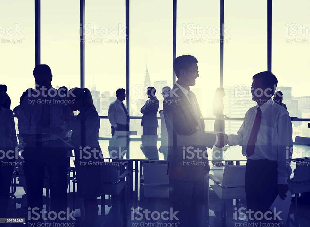 Business people shaking hands in an office building against a New...