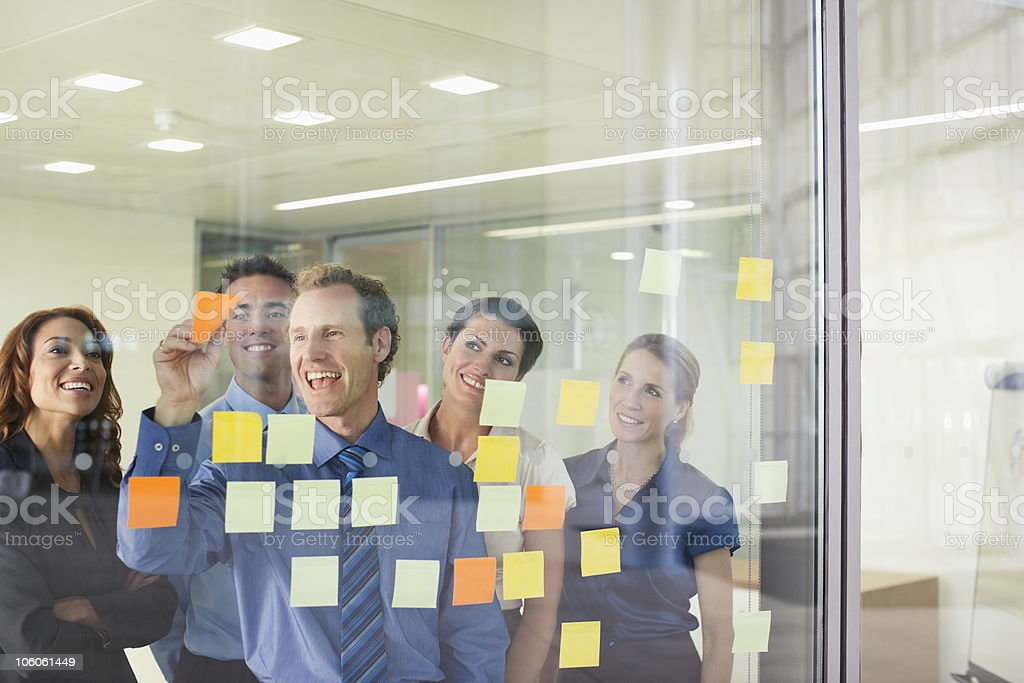 Group of business people looking at adhesive papers royalty-free stock photo