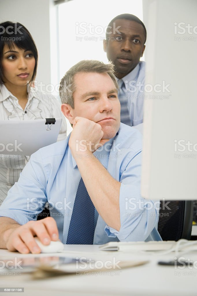Group of business people looking at computer screen in office stock photo