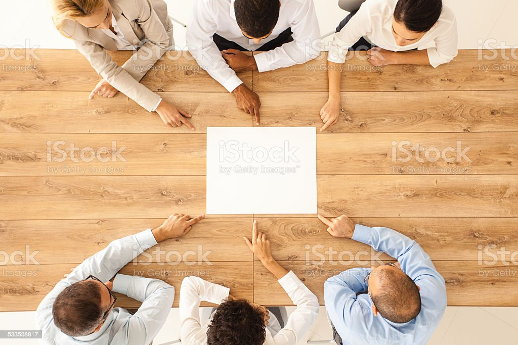 Group of business people pointing at blank paper stock photo