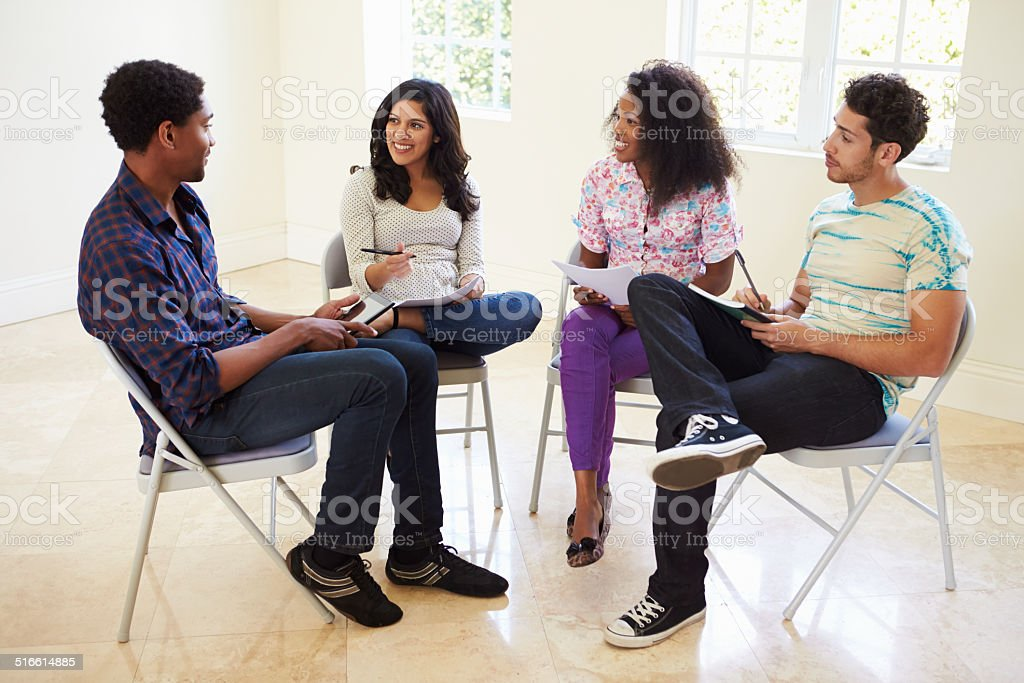 Group Of Business People Sitting On Chairs Having Meeting stock photo