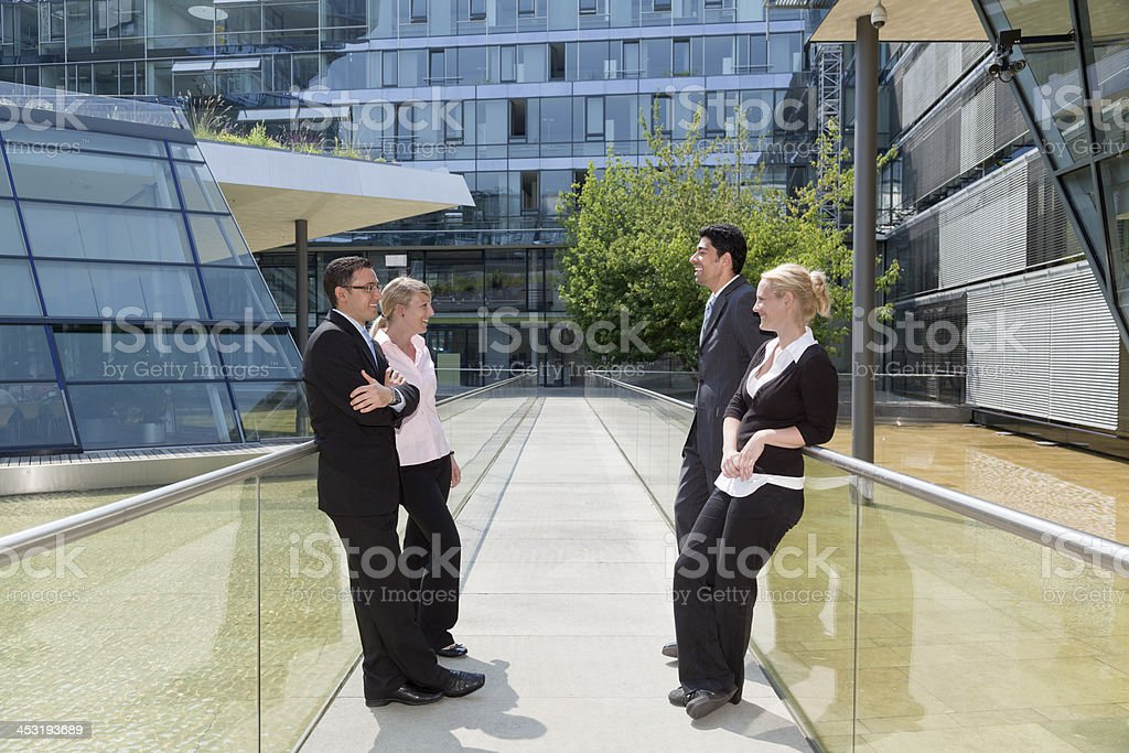 Group of business people talking outdoors in sunlight royalty-free stock photo