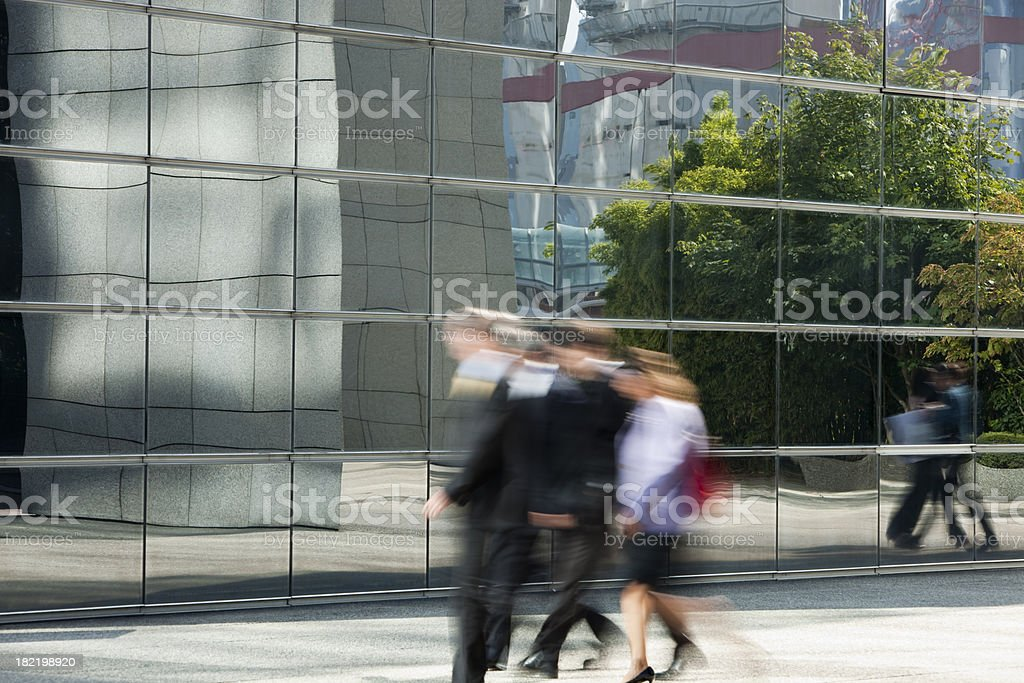 Group of business people walking against a glass wall royalty-free stock photo