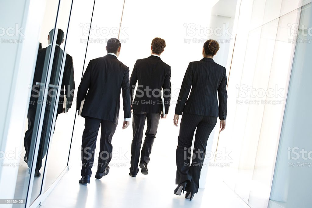 group of business people walking away stock photo