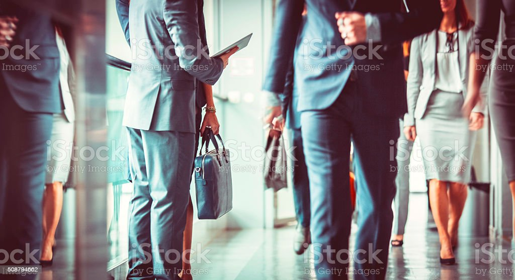 Group of business people walking in the office building lobby stock photo