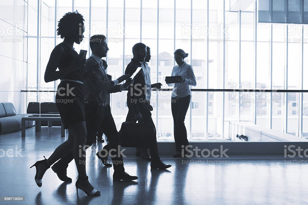 Group of business people walking in the office building stock photo