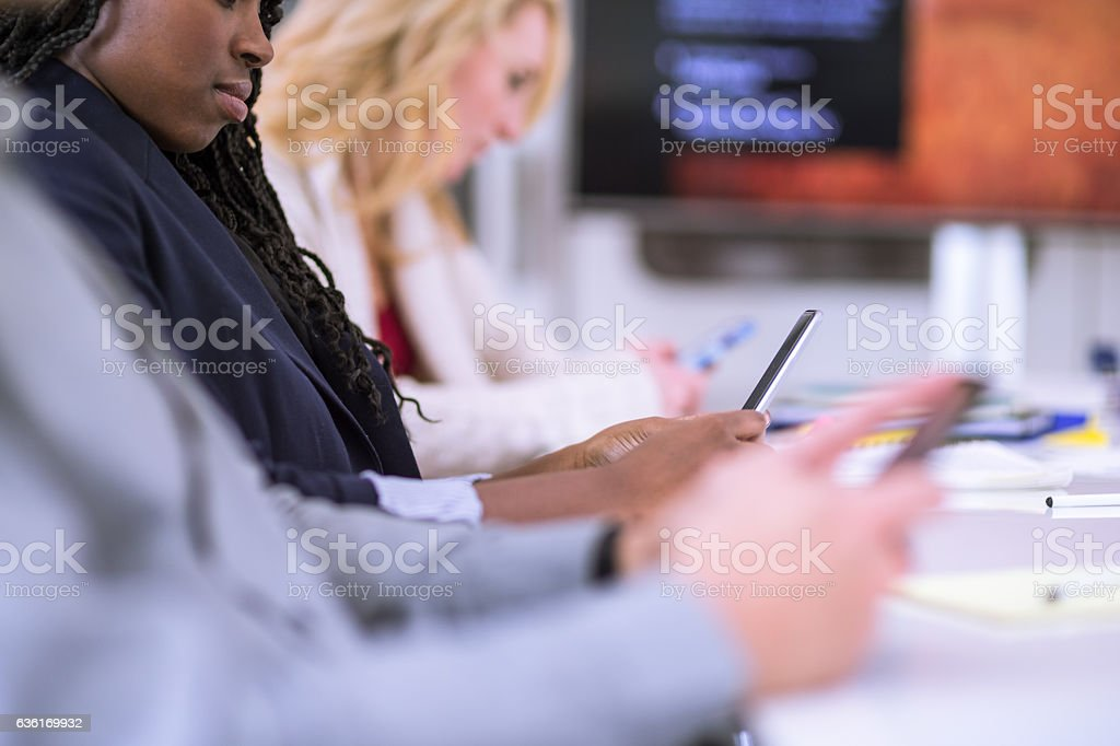 Group of business teammembers texting on their mobile phones stock photo