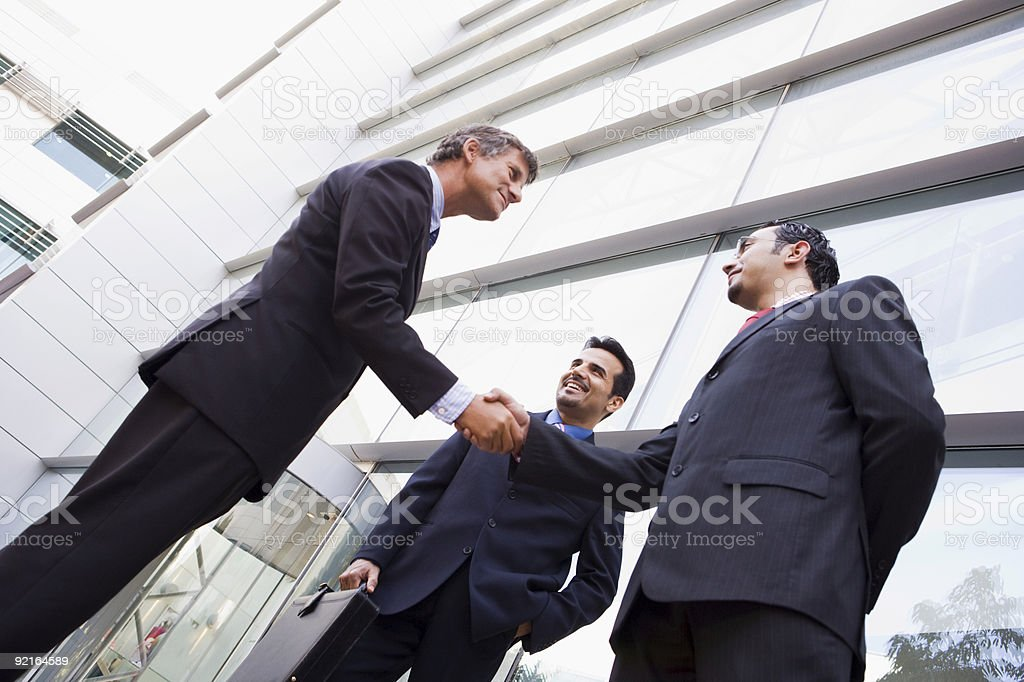 Group of businessmen shaking hands outside office royalty-free stock photo