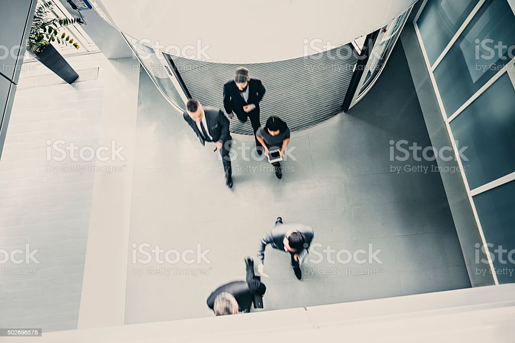 Group of  businesspeople entering the lobby stock photo