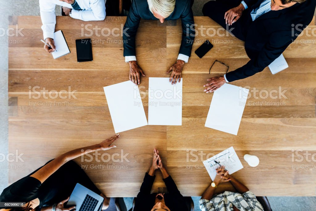 Group of businesspeople placing blank placards on table stock photo