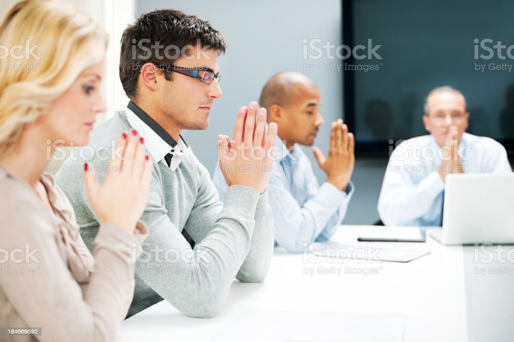 Group of businesspeople pray in a office. royalty-free stock photo