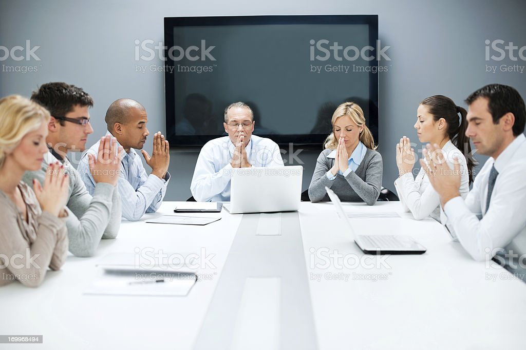 Group of businesspeople pray on a meeting. stock photo