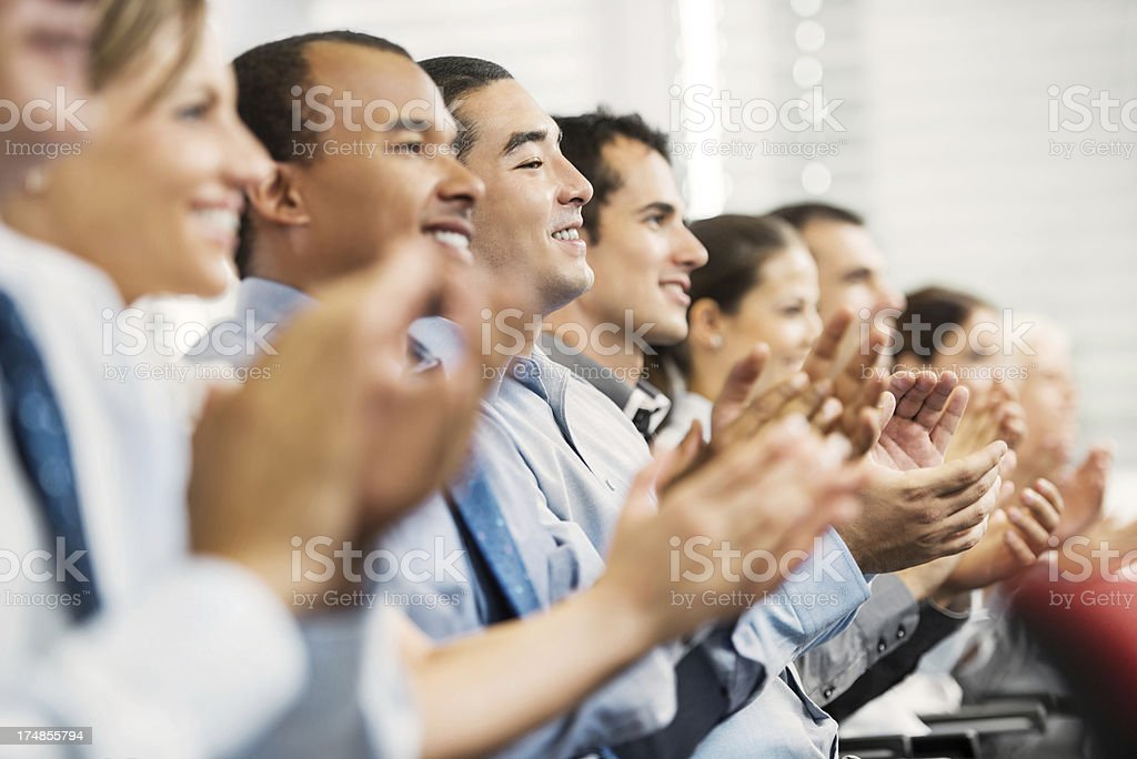 Group of businesspeople sitting in a line and applauding. royalty-free stock photo