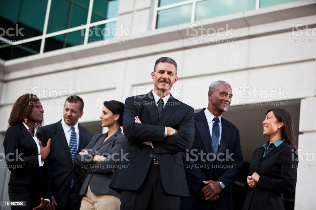 Group of businesspeople talking outside office building royalty-free stock photo