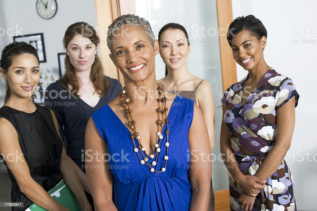 Group of businesswomen in an office smiling stock photo