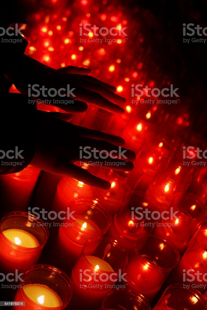 Group of candles with two hands silhouetted. stock photo