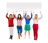 Group of casual young women holding blank white board overhead