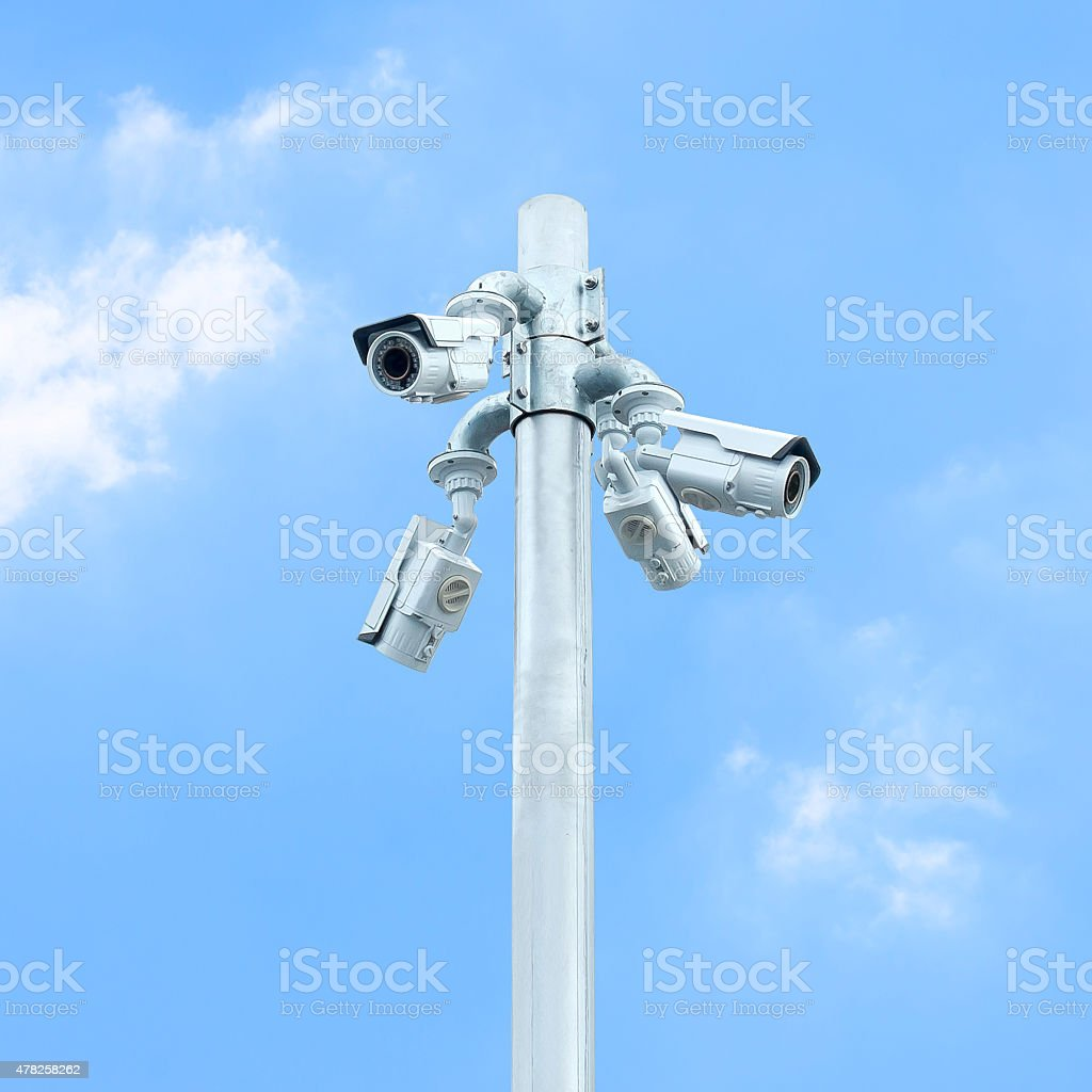 Group of CCTV on post with cloudy blue sky stock photo