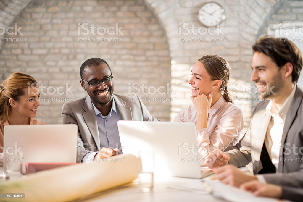 Group of cheerful business colleagues talking on a meeting. stock photo