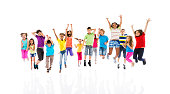 Group of cheerful children jumping with arms raised.