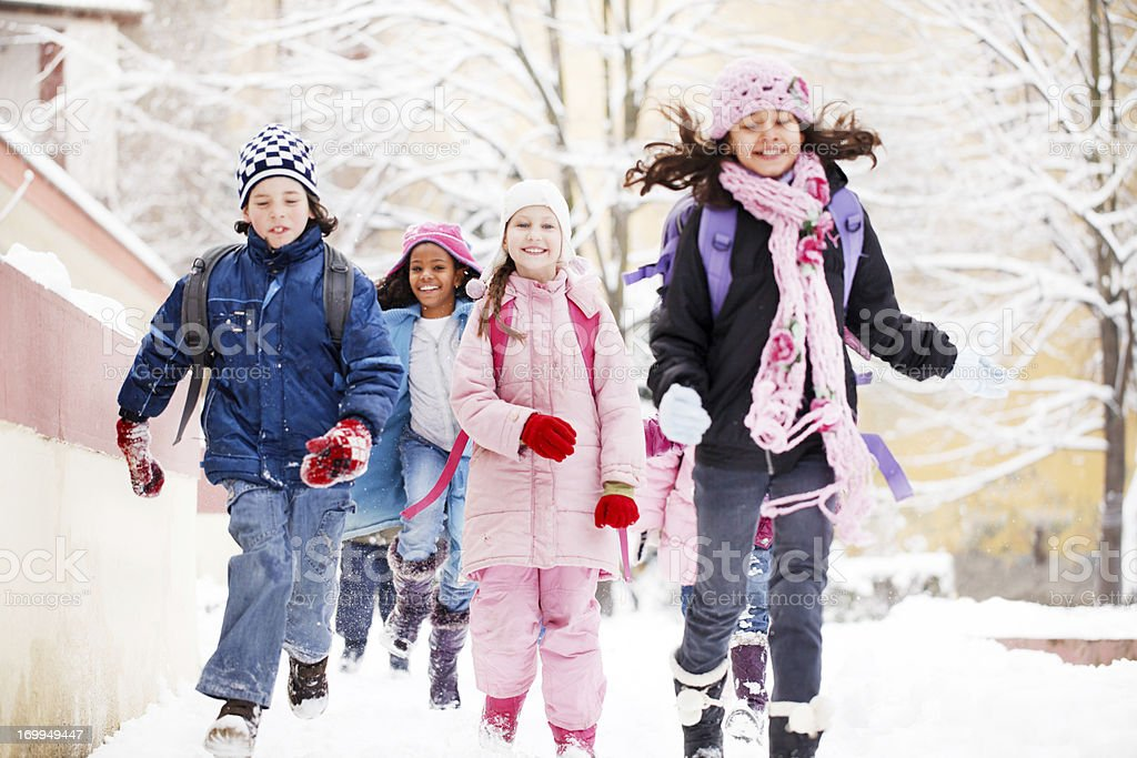 Group of cheerful children running in the snow. stock photo