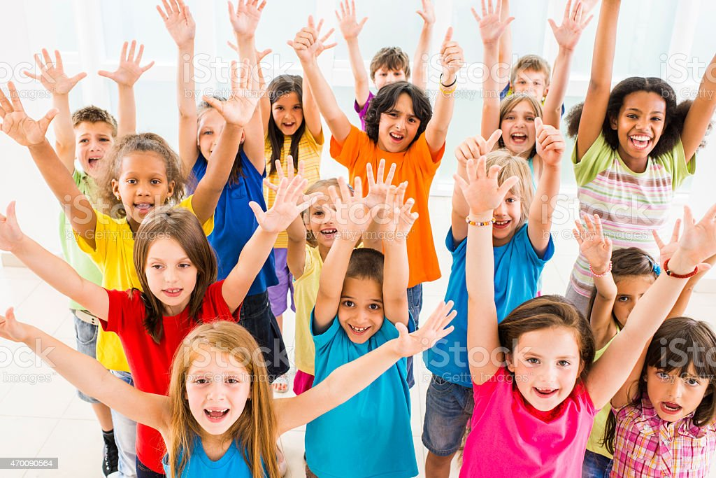Group of cheerful children with raised arms looking at camera. stock photo