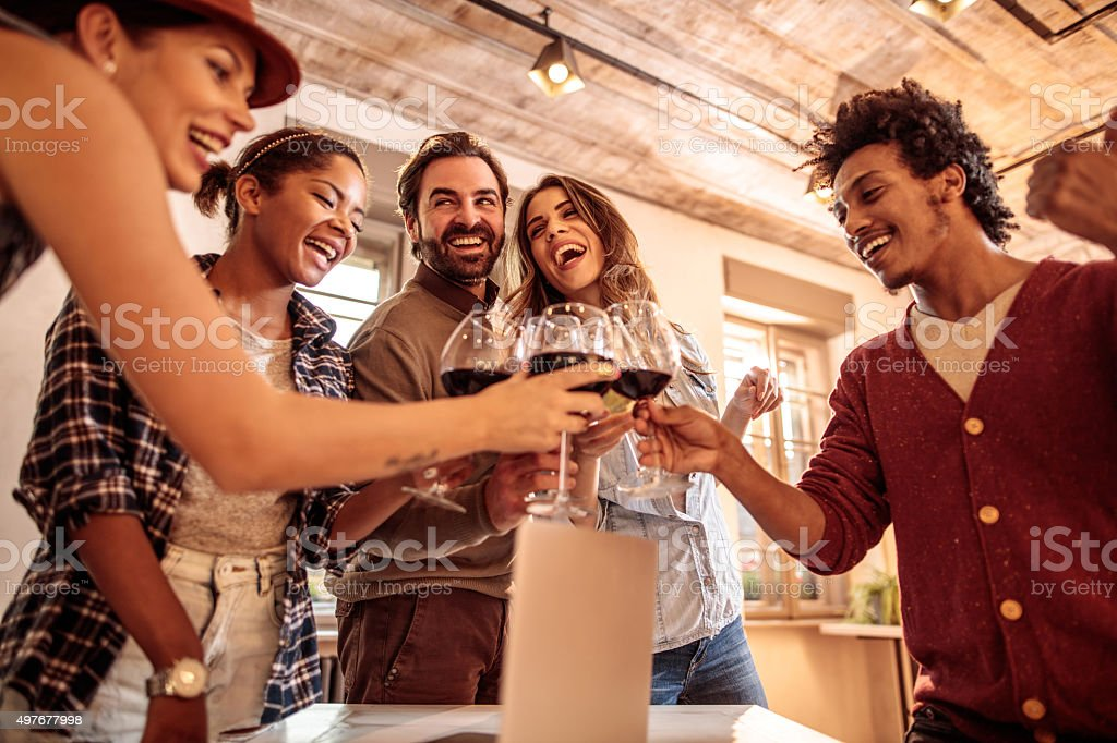 Group of cheerful colleagues toasting with wine in the office. stock photo