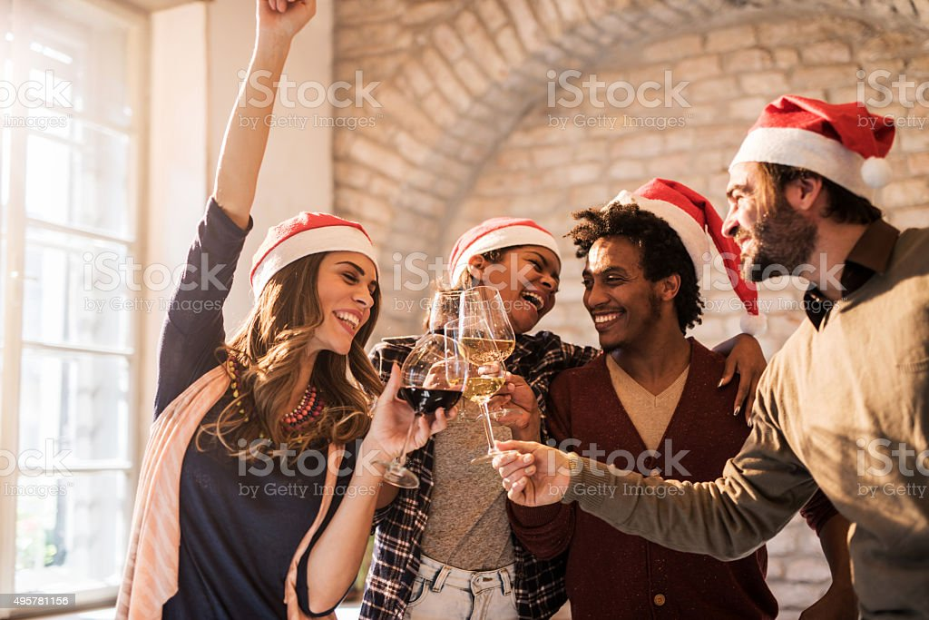 Group of cheerful friends toasting to upcoming New Year. stock photo