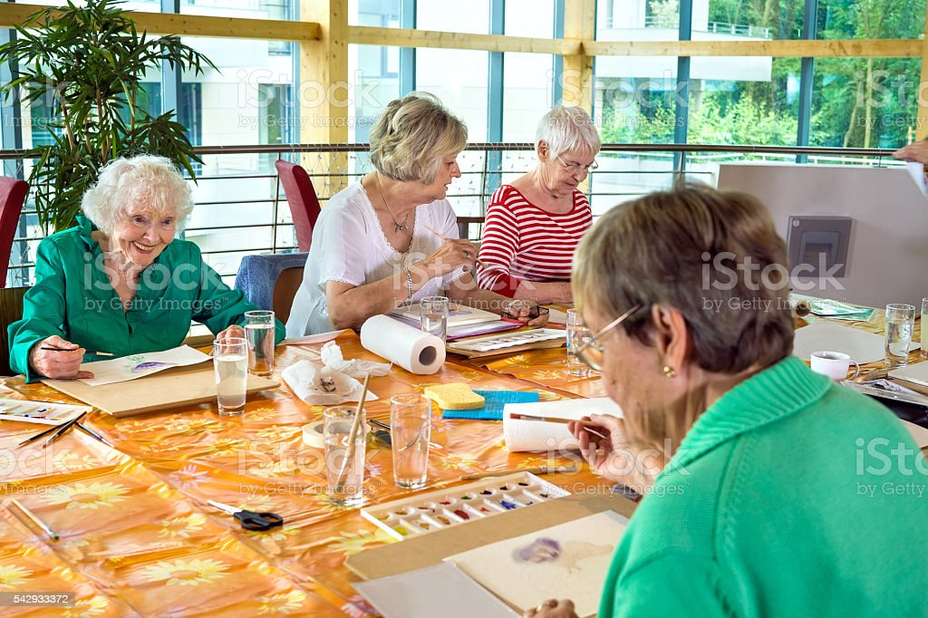 Group of cheerful older students painting together. stock photo