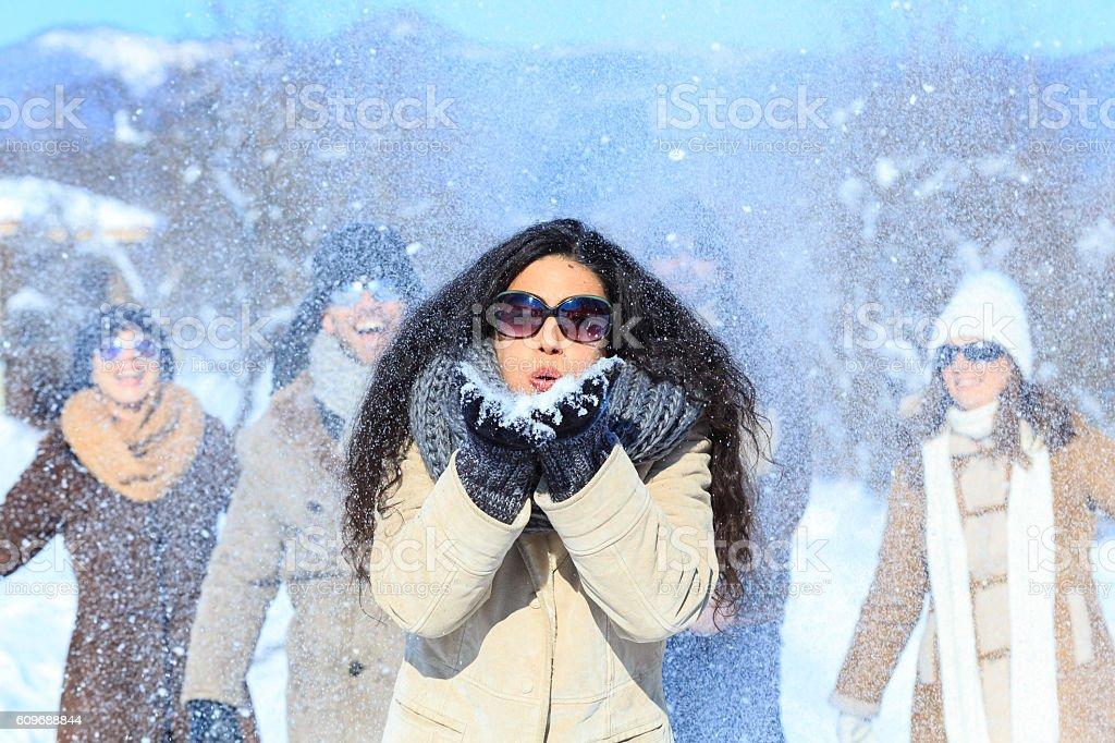 Group of cheerful people having fun on snow mountain stock photo