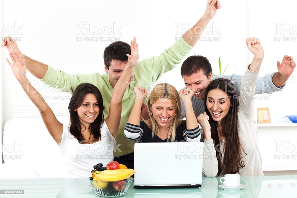 Group of cheerful people working on laptop with hands raised royalty-free stock photo