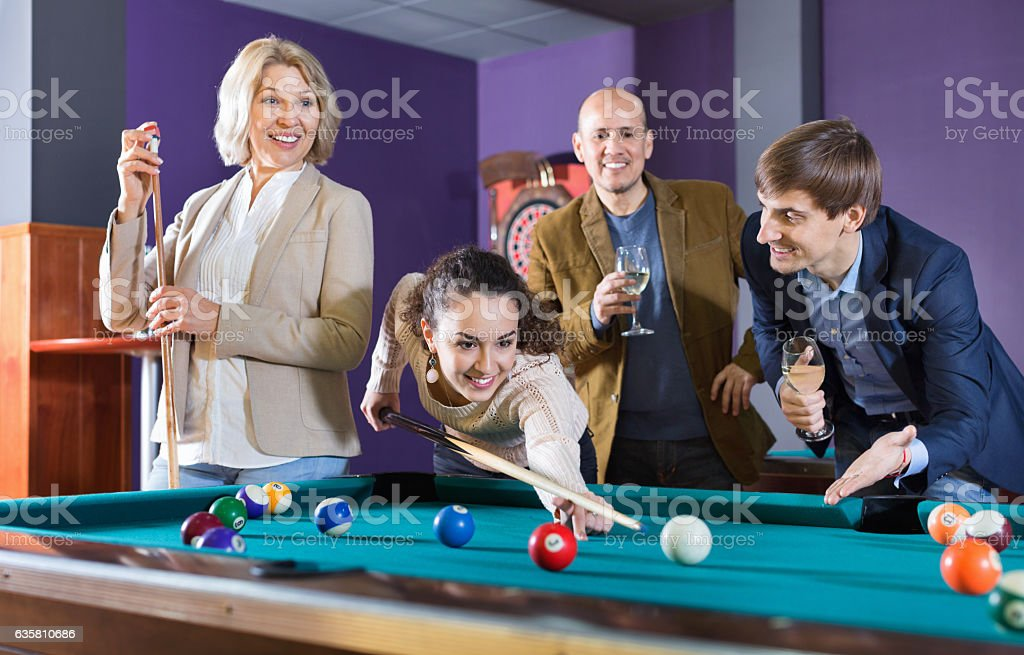 Group of cheerful pretty positive friends playing billiards stock photo