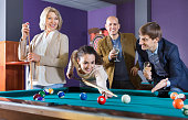 Group of cheerful pretty positive friends playing billiards