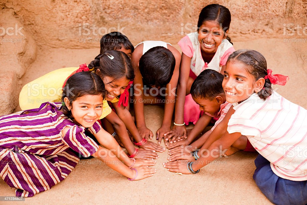Group of Cheerful Rural Indian Children joining hands stock photo