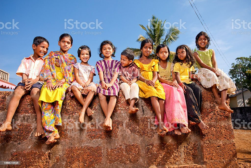 Group of Cheerful Rural Indian Children Sitting on a Wall royalty-free stock photo