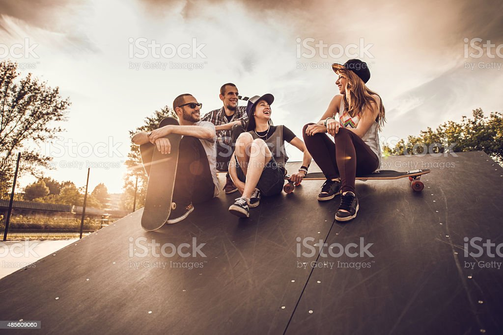 Group of cheerful skateboarders talking on a skate ramp. stock photo