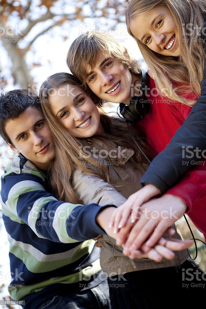 Group of cheerful teenagers joining their hands royalty-free stock photo