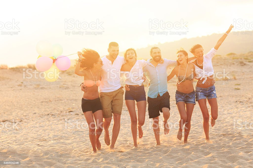 Group of cheerful young people running on the beach stock photo