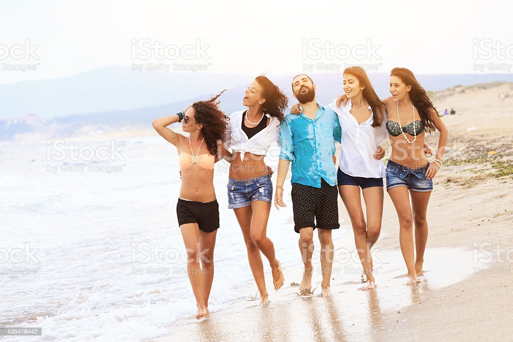 Group of cheerful young people walking on the beach stock photo