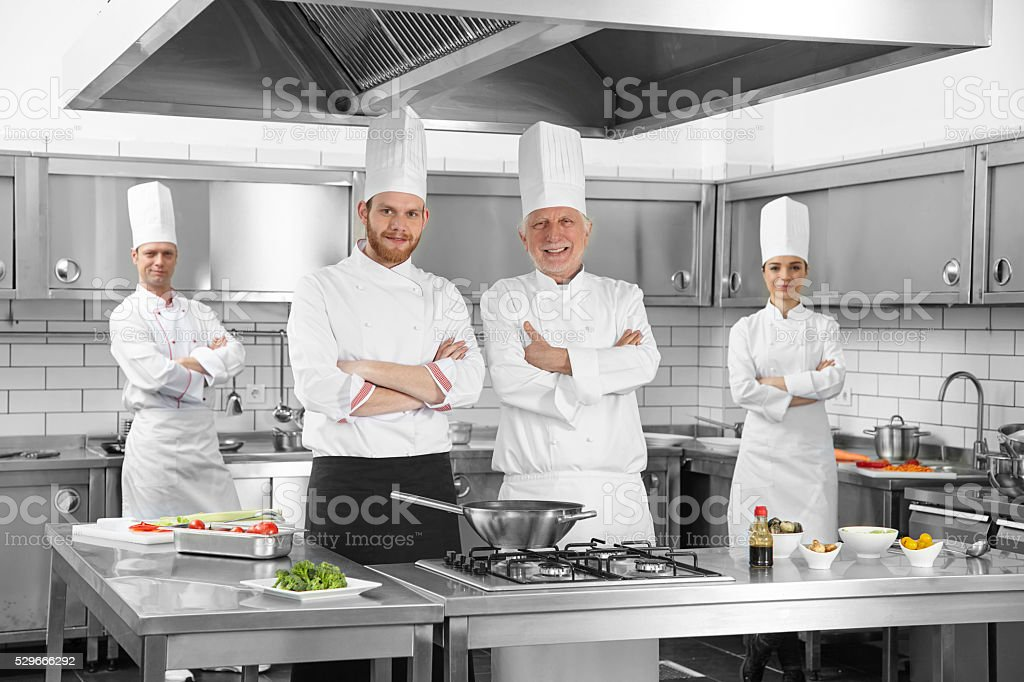 Group of chefs cooking in kitchen stock photo