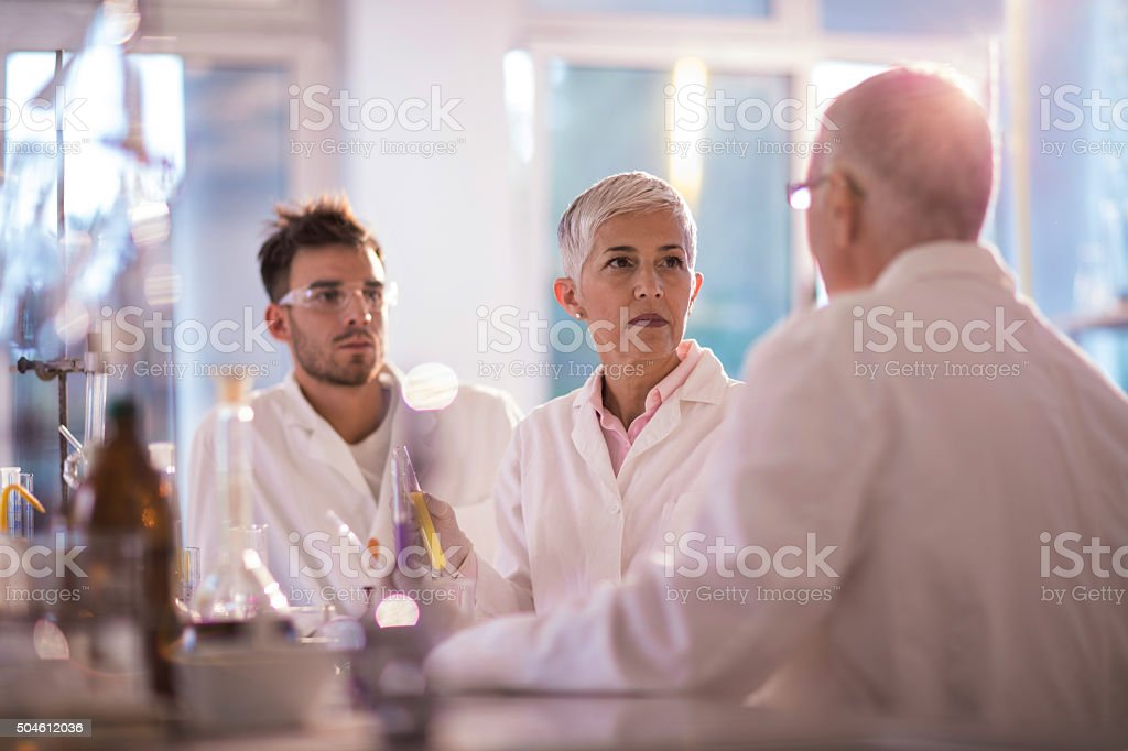 Group of chemists sitting in laboratory and communicating. stock photo