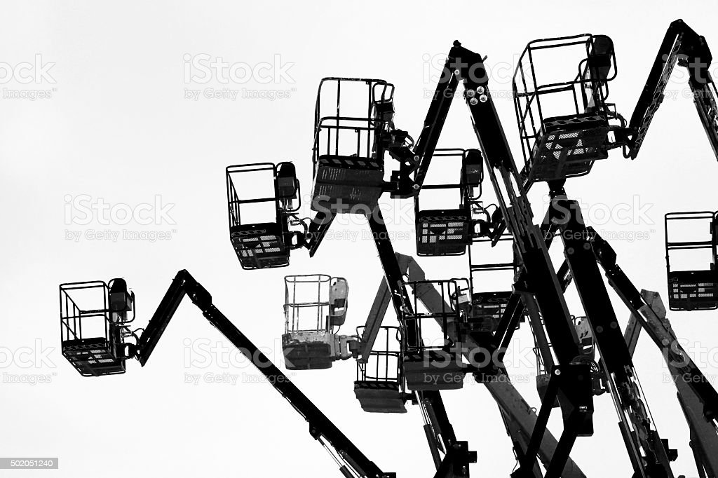 Group of cherry pickers silhouetted. stock photo
