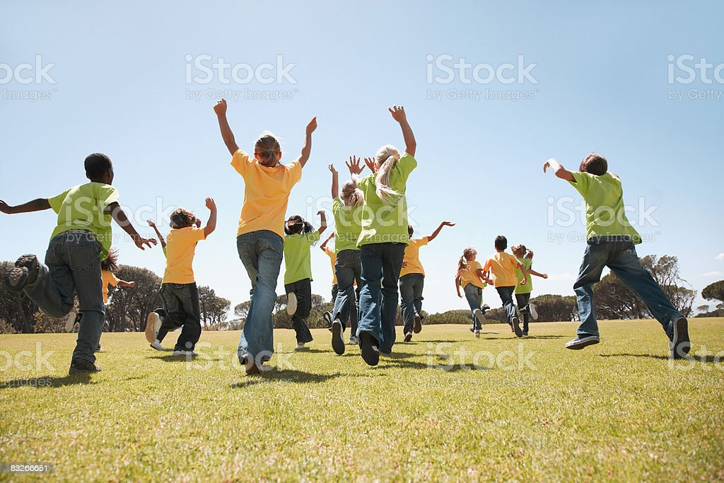 Group of children cheering and running in park royalty-free stock photo